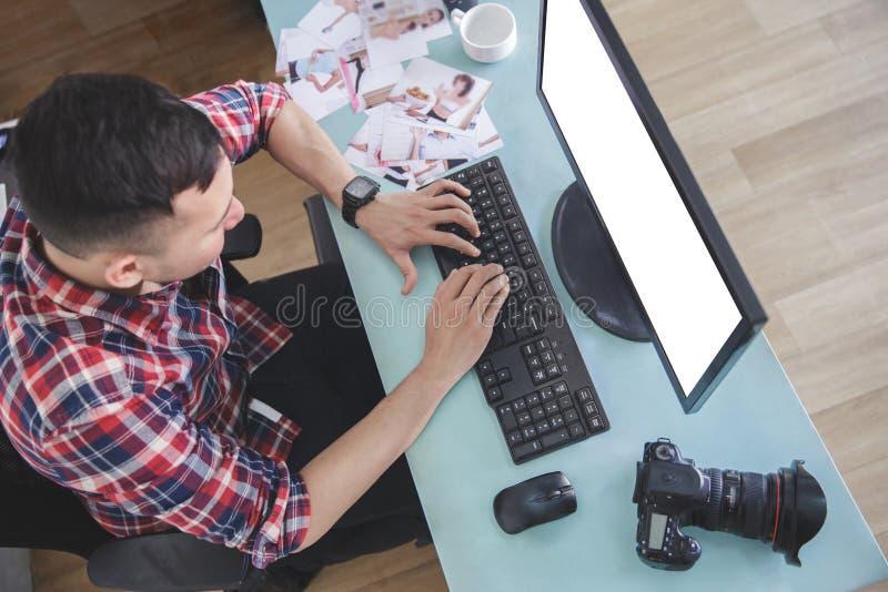 Junger Fotograf, der auf seinem Computer nach Fotosession schreibt lizenzfreies stockbild
