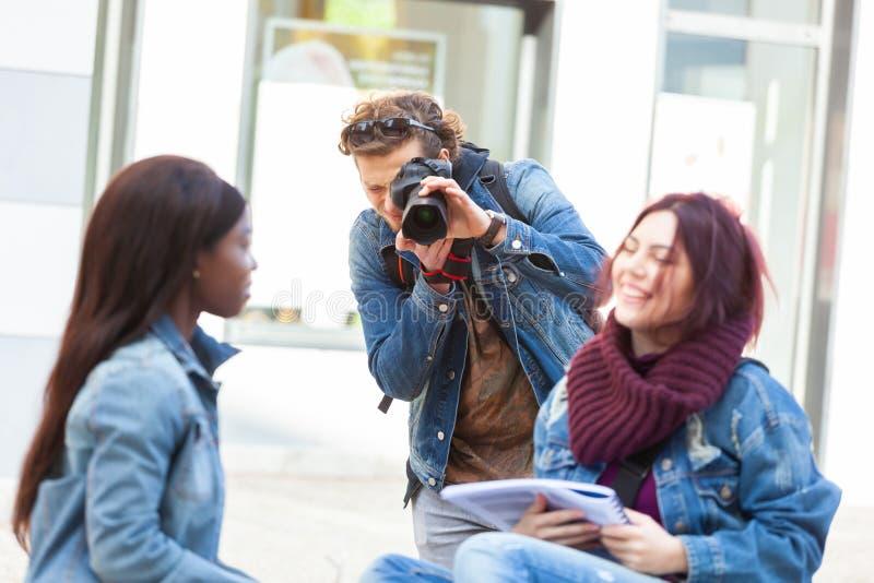 Junger Fotograf, der Fotos von zwei Mädchen beim Studieren macht stockfotografie