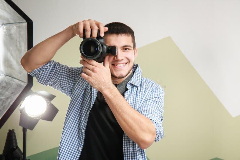Junger Fotograf, der im Studio arbeitet lizenzfreie stockfotografie
