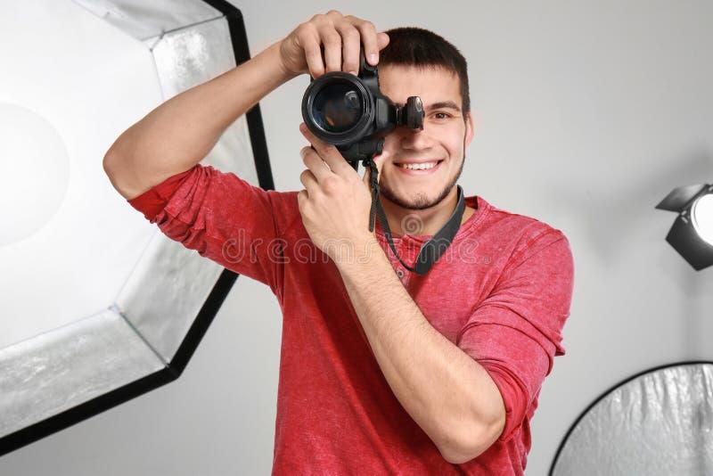 Junger Fotograf, der in profe sional Studio arbeitet lizenzfreie stockfotos