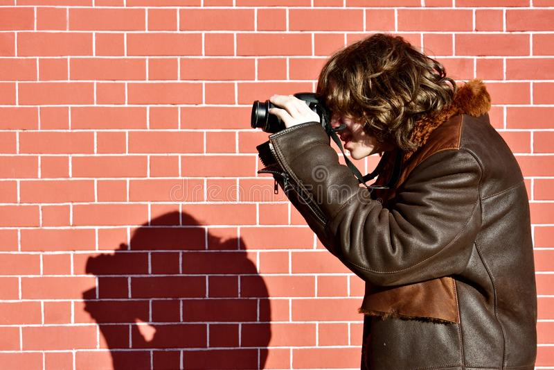 Junger Fotograf fokussiert seine Kamera gegen Backsteinmauer stockbilder