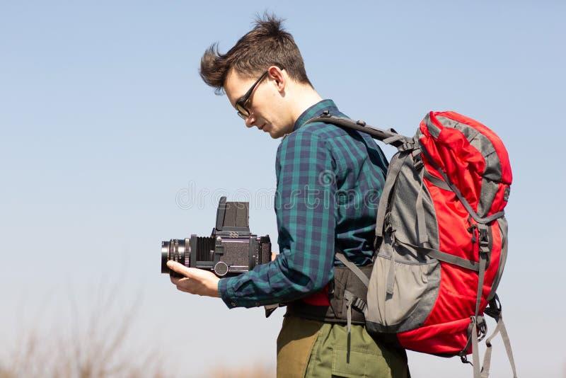 Junger Fotograf mit einem Rucksack und eine Weinlesekamera auf der Suche nach malerischen Plätzen lizenzfreie stockfotografie