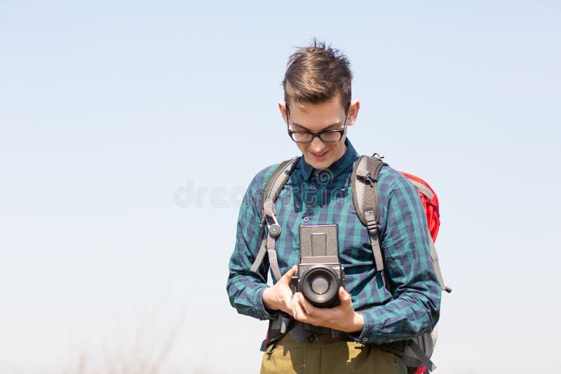Junger Fotograf mit einem Rucksack und eine Weinlesekamera auf der Suche nach malerischen Pl?tzen stockbild