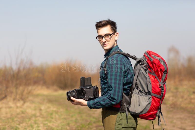 Junger Fotograf mit einem Rucksack und eine Weinlesekamera auf der Suche nach malerischen Pl?tzen lizenzfreies stockbild
