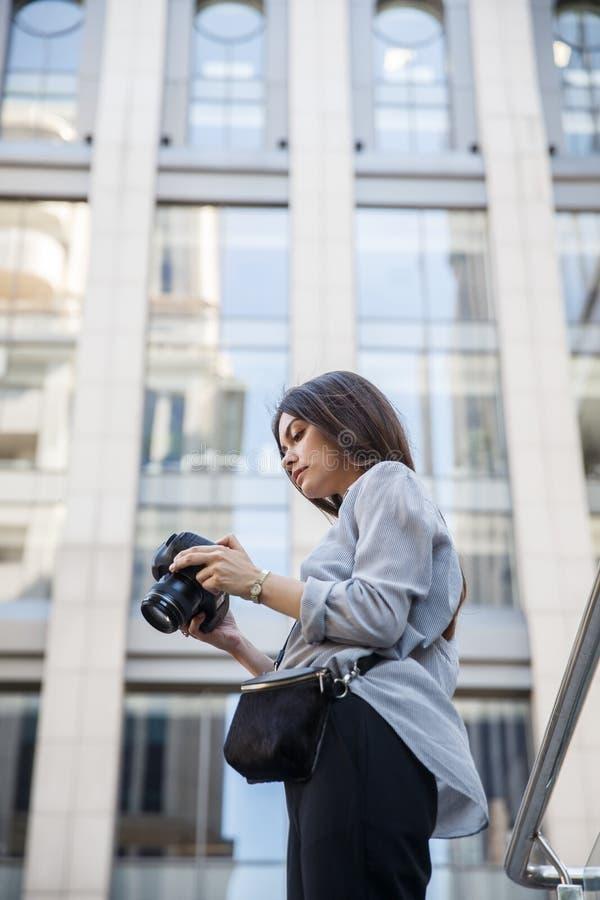Junger Fotograf sieht Fotos auf ihrer Kamera an Großes städtisches Gebäude am Hintergrund lizenzfreie stockfotos