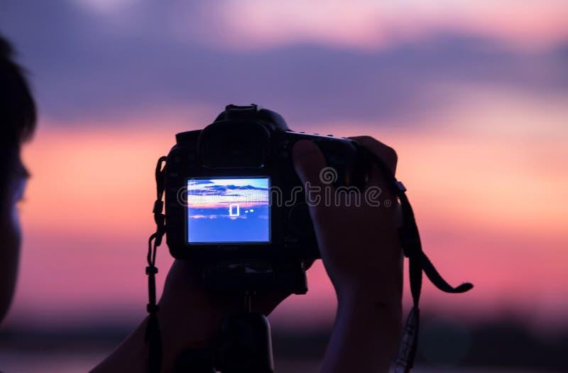 Junger Fotograf und Spiegelreflexkamera auf Stativ nahe der Lagune stockbilder