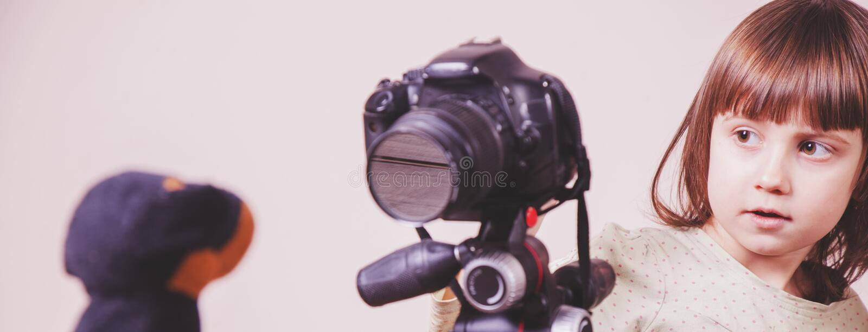 Junger Fotograf Wenig nettes Kindermädchen, das Foto des Spielzeughundes mit einer DSLR-Kamera macht Selektiver Fokus auf Auge stockbild