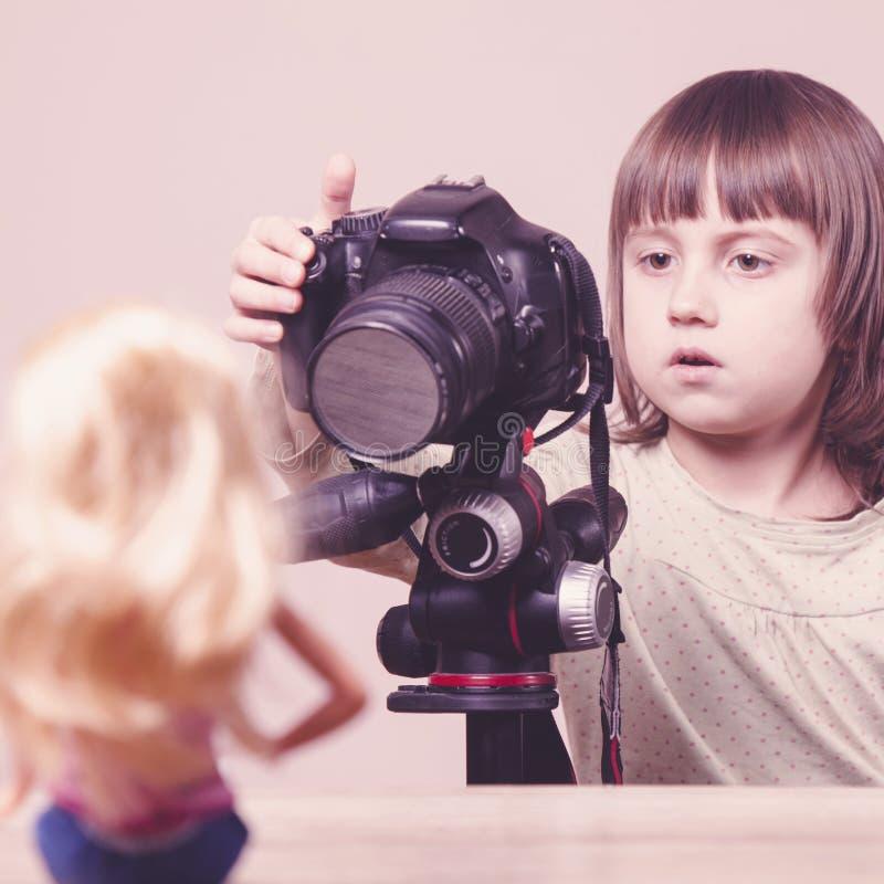Junger Fotograf Wenig nettes Kindermädchen schießt Spielzeugpuppe lizenzfreie stockbilder