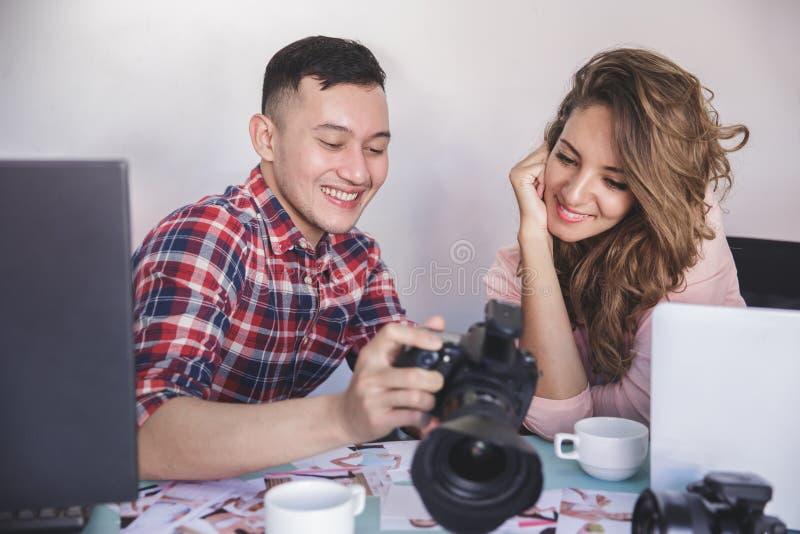 Junger Fotografanteil das Fotoergebnis mit seinem Modell stockbilder