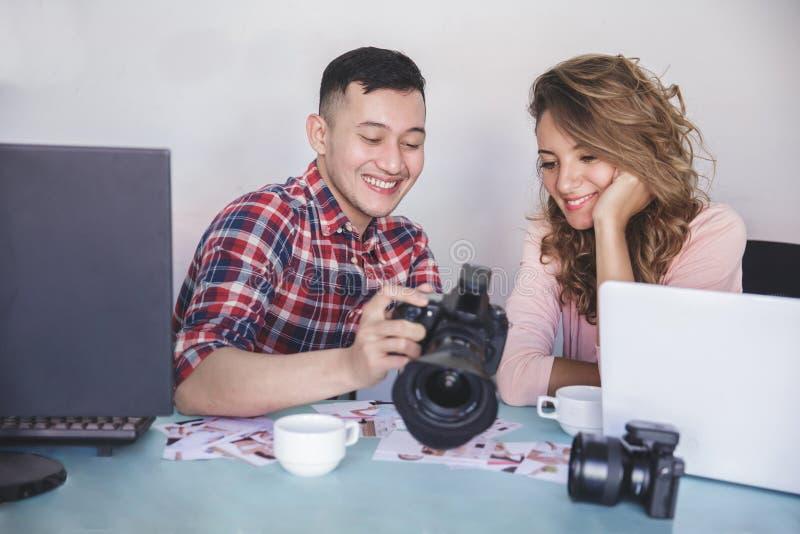 Junger Fotografanteil das Fotoergebnis mit seinem Modell stockfoto