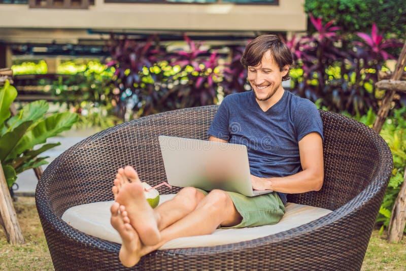Junger Freiberufler, der im Urlaub nahe bei dem Swimmingpool arbeitet stockfoto