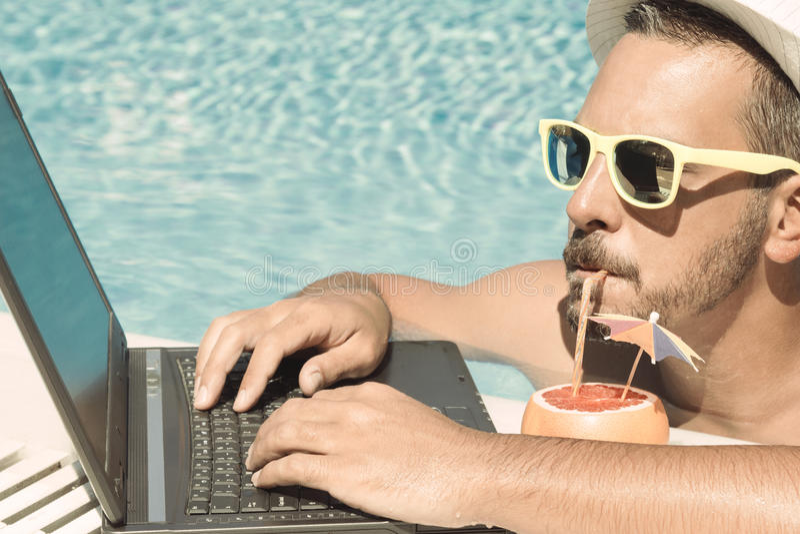 Junger Freiberufler, der im Urlaub nahe bei dem Swimmingpool arbeitet lizenzfreie stockfotografie