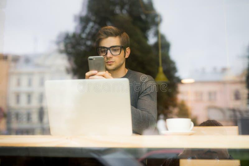 Junger Freiberufler des gutaussehenden Mannes Schreibensms oder Gebrauchstelefon vor Laptopansicht vom Fenster lizenzfreie stockbilder