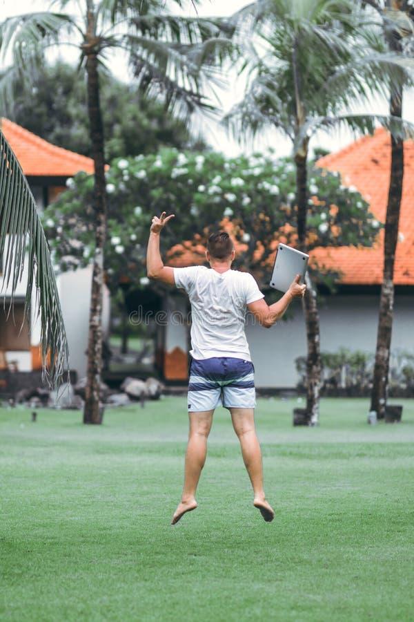 Junger Freiberuflermann, der mit Laptop im tropischen Park von Bali-Insel springt stockbild