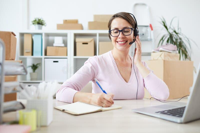 Junger freundlicher Betreiber des Call-Centers oder des on-line-Geschäftes, die Anmerkungen machen stockfotografie