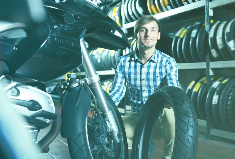 Junger froher Mannkunde, der sein Motorrad hält lizenzfreie stockfotos