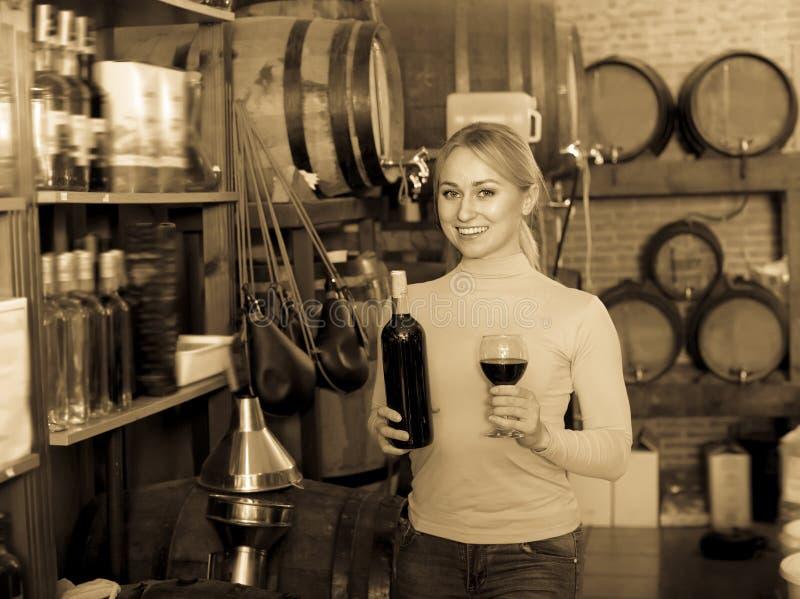 Junger froher weiblicher Kunde, der Flasche Wein nimmt stockbilder