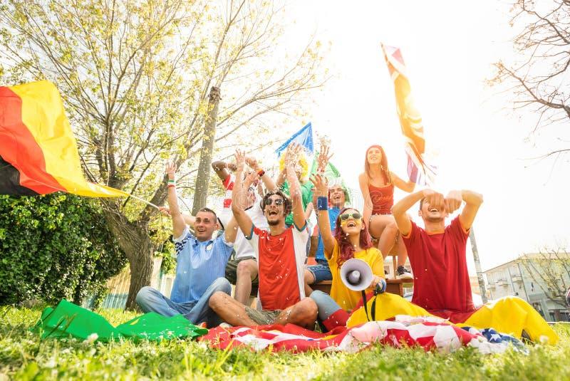 Junger Fußballanhänger lockert das Zujubeln mit internationalen Flaggen auf stockbilder