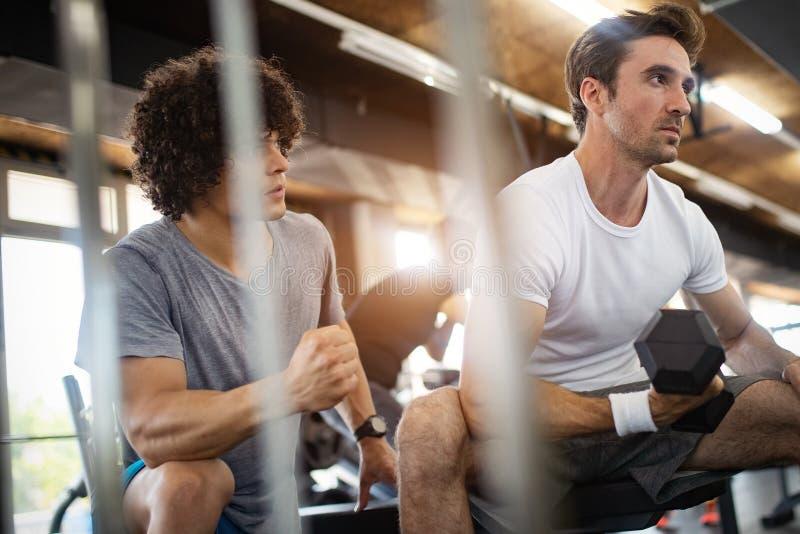 Junger geeigneter Mann, der Training mit einem pers?nlichen Trainer tut stockbild