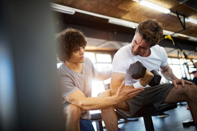 Junger geeigneter Mann, der Training mit einem pers?nlichen Trainer tut stockfoto