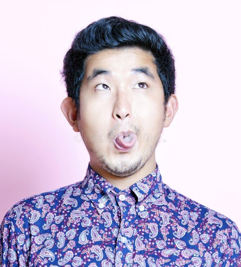 Junger Geeky asiatischer Mann im bunten Hemd, das lustiges Gesicht zieht stockbilder