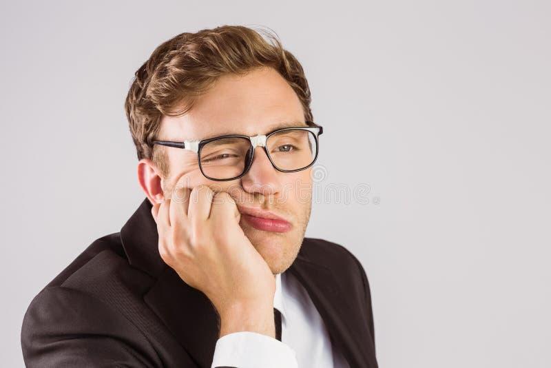Junger geeky Geschäftsmann, der gebohrt schaut lizenzfreies stockfoto
