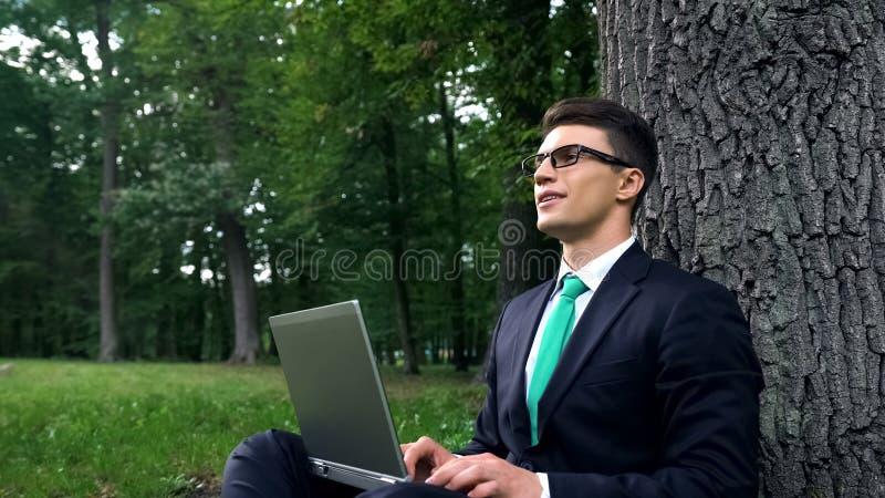Junger Geschäftsmann, der Arbeit im Natur-, Freiheits- und Inspirationskonzept genießt lizenzfreie stockbilder