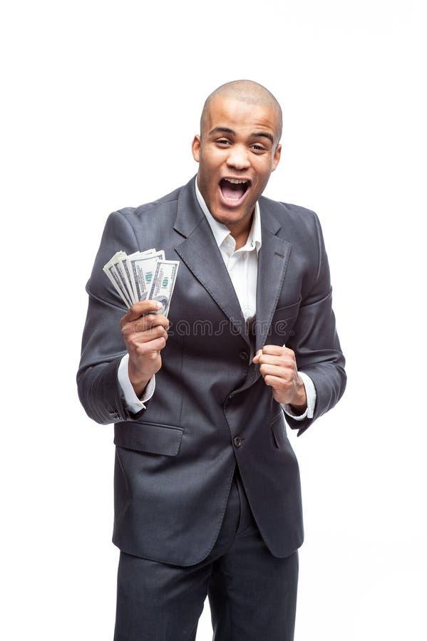 Junger Geschäftsmann in der Klage, die Geld lokalisiert auf weißem Hintergrund hält stockbilder