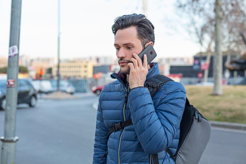 Junger Geschäftsdurchschnittsbürger, der auf einem Mobiltelefon und einem Matrosen spricht stockbild