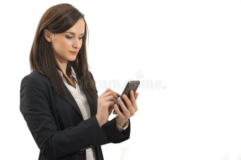 Junger Geschäftsfraublick auf das Mobiltelefon lokalisiert stockfotografie