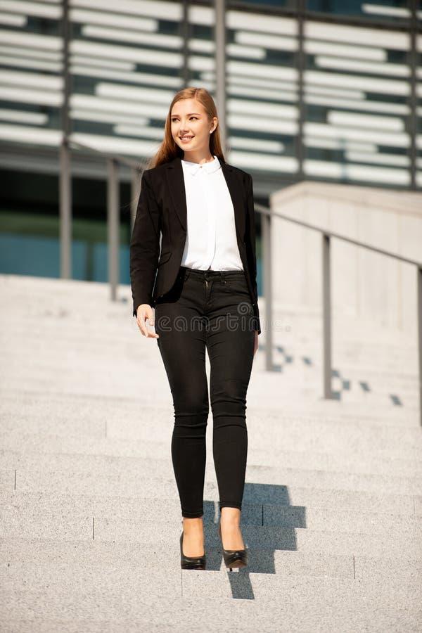 Junger Geschäftsfrauweg auf der Treppe, die Bürogebäude verlässt lizenzfreies stockfoto