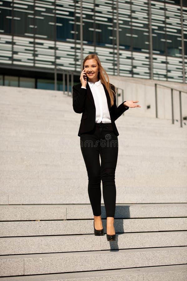 Junger Geschäftsfrauweg auf der Treppe, die Bürogebäude verlässt und lizenzfreie stockfotografie