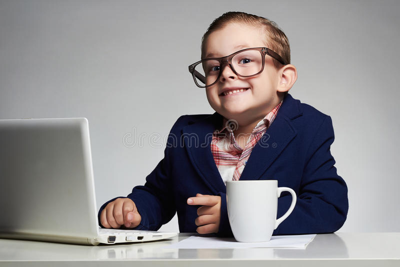 Junger Geschäftsjunge lächelndes Kind in den Gläsern kleiner Chef im Büro stockfotografie