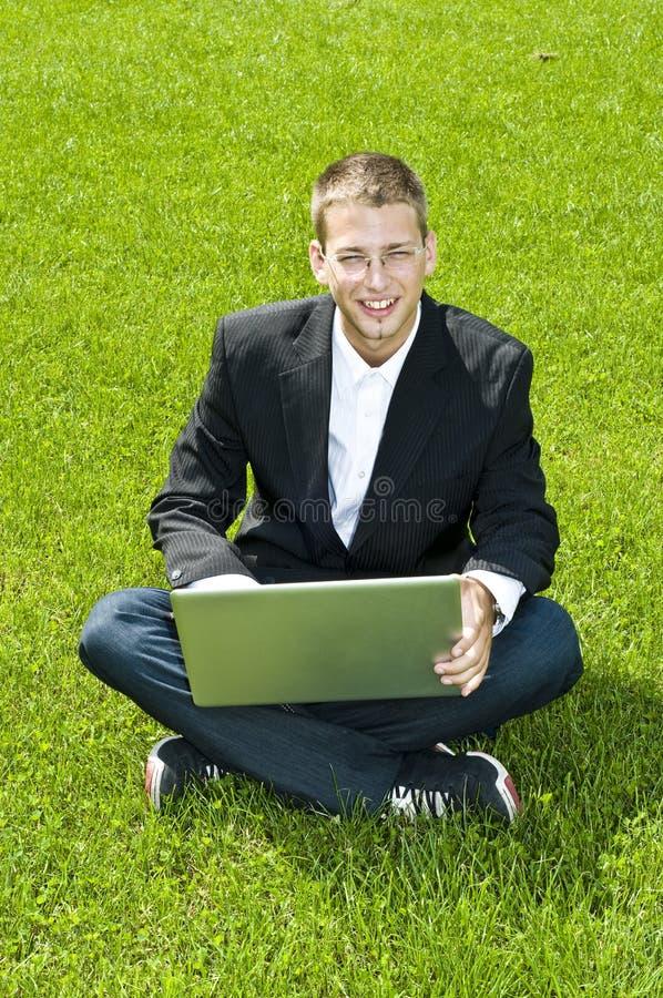 Junger Geschäftsmann auf dem Gras mit seinem Laptop lizenzfreie stockbilder