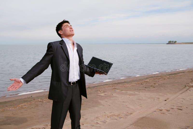 Junger Geschäftsmann auf dem Strand stockbilder