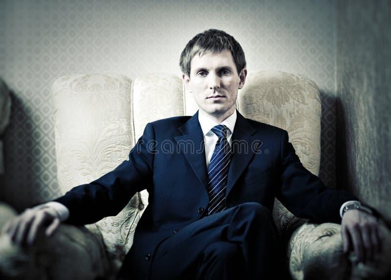 Junger Geschäftsmann auf einem Stuhl lizenzfreies stockfoto