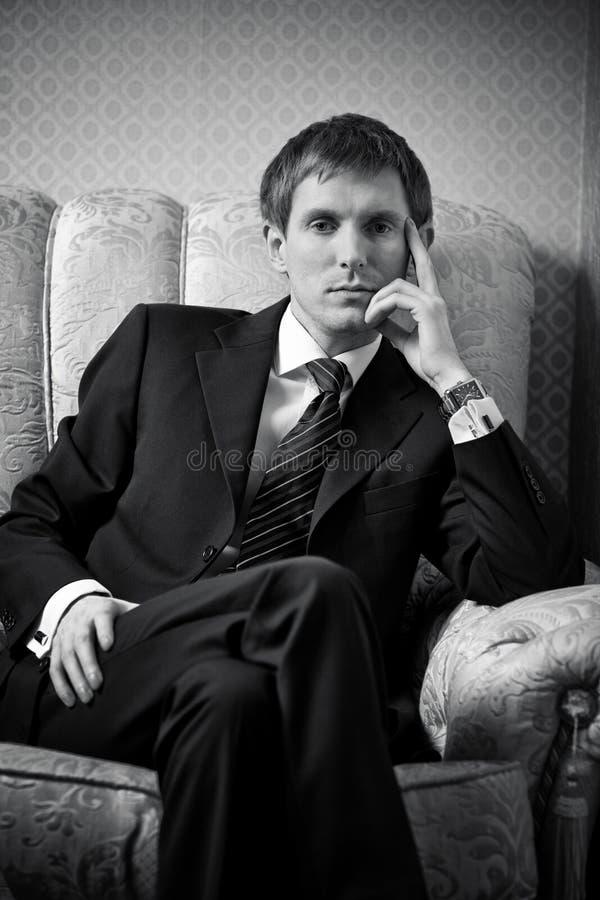 Junger Geschäftsmann auf einem Stuhl lizenzfreies stockbild