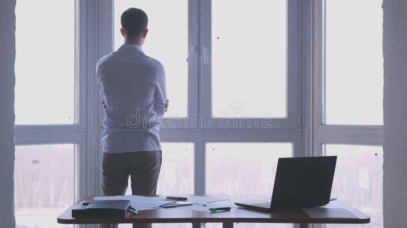 Junger Geschäftsmann bewundern Ansicht vom Fenster in einem Büro stockbild