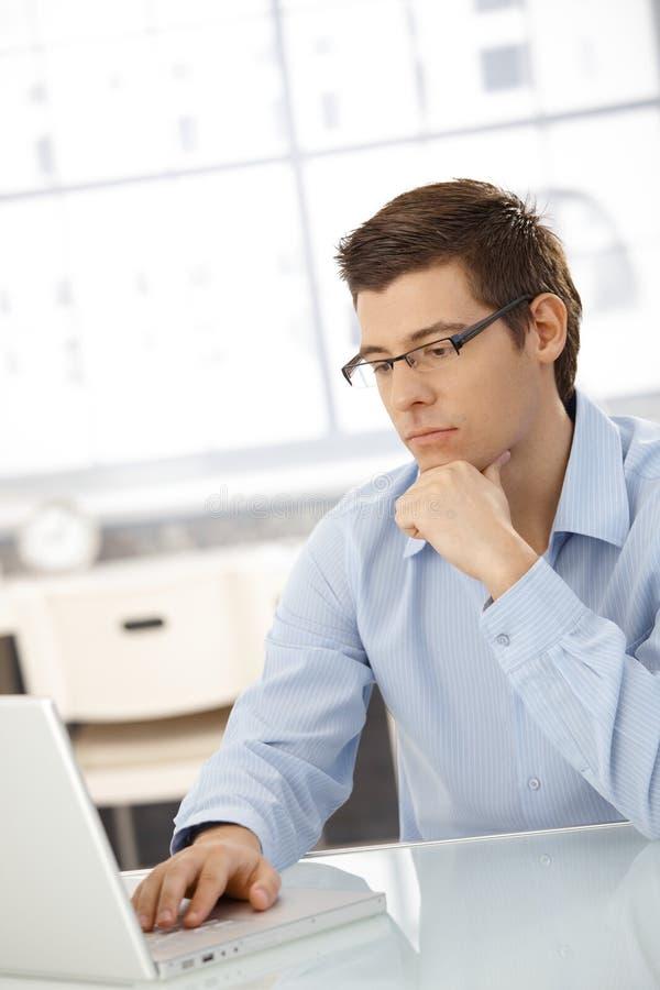 Junger Geschäftsmann, der auf Computerarbeit sich konzentriert stockfotografie