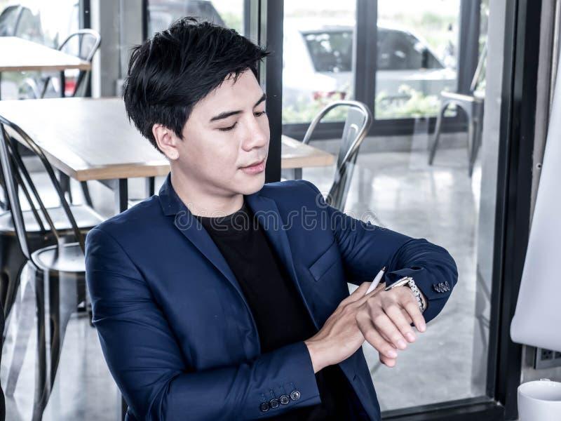 Junger Geschäftsmann, der auf seine Uhrwartezeit für jemand aufpasst lizenzfreies stockfoto