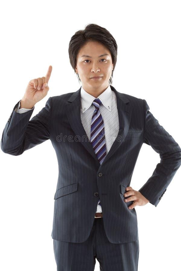 Junger Geschäftsmann, der aufwärts zeigt stockfotografie