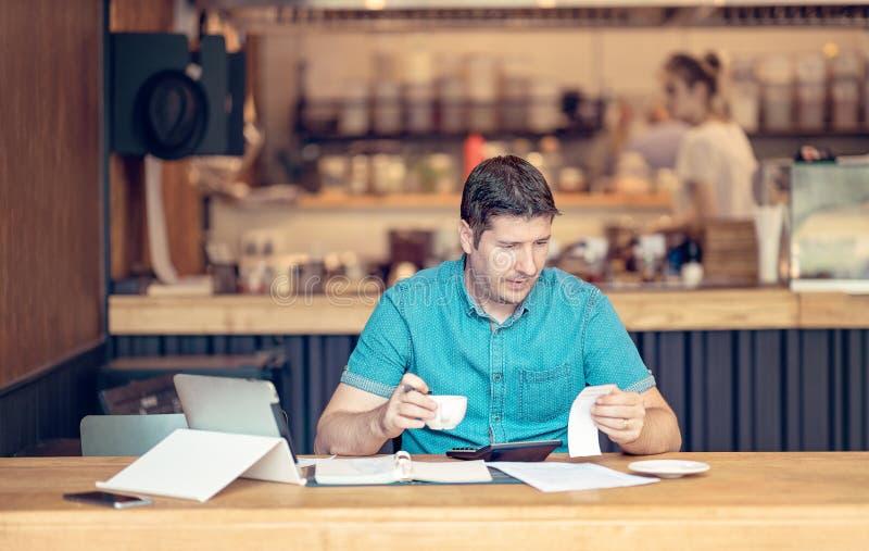 Junger Geschäftsmann, der Bücher an einem Tisch während eines Spät- in seinem Restaurant tut Junger Startinhaber, der gesorgt sch stockfotografie
