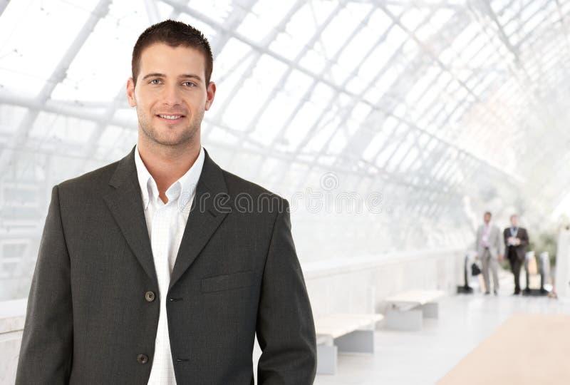 Junger Geschäftsmann in der Bürovorhalle stockbild