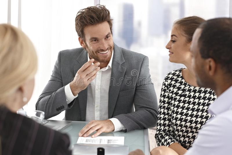 Junger Geschäftsmann, der bei der Sitzung spricht stockfotografie