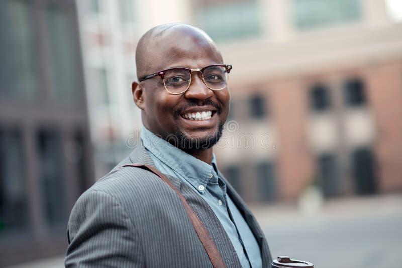 Junger Geschäftsmann, der breit während Gefühl motiviert lächelt lizenzfreies stockfoto