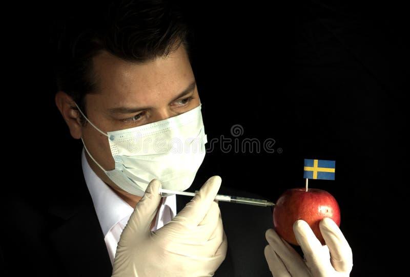 Junger Geschäftsmann, der Chemikalien in einen Apfel mit Schweden einspritzt stockbild