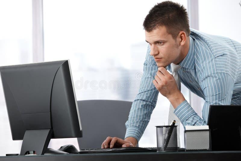 Junger Geschäftsmann, der an Computer arbeitet stockfoto