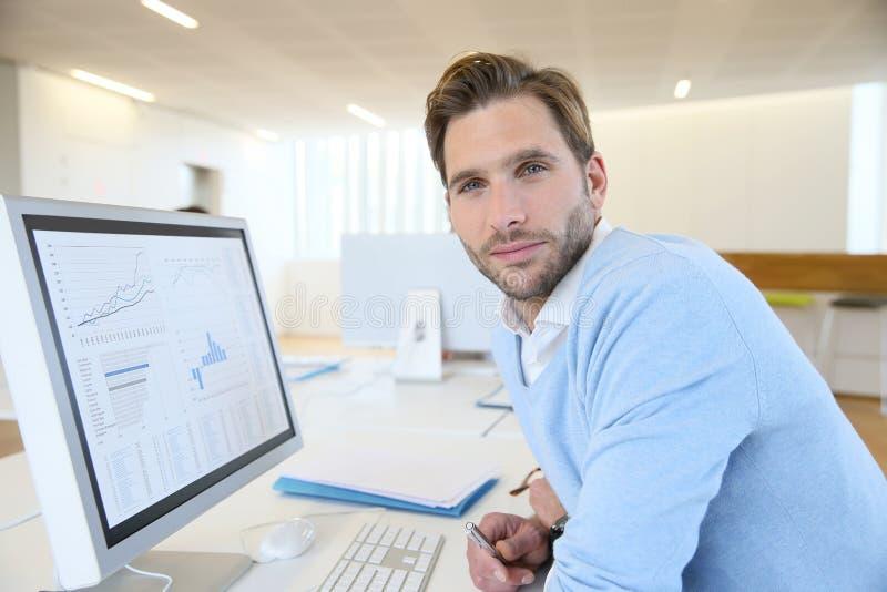 Junger Geschäftsmann, der an Computer im Büro arbeitet stockbild