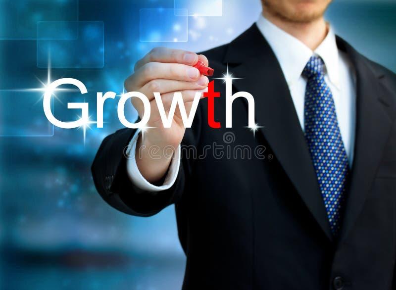 Junger Geschäftsmann, der das Wort Wachstum schreibt stockbild