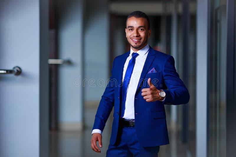 Junger Geschäftsmann, der den Erfolg, Daumen herauf GE zeigend feiert stockfotos
